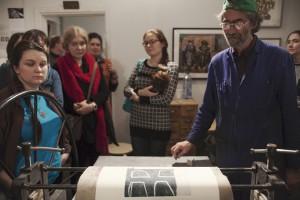 mit Druckergebnis an Druckmaschine inmitten von TeilnehmerInnen, 31.10.2015, Foto: K. Snigirevskaya